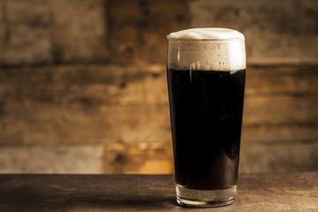 Black beer on wooden background