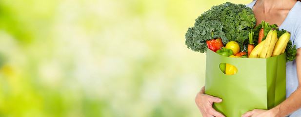 Woman hands with grocery bag of vegetables.