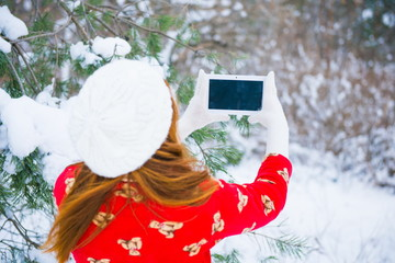 woman photographed on the tablet in the winter forest
