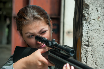concentrated young brunette looking in rifle sight