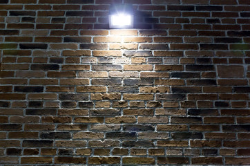 spotlight on red brick wall at night
