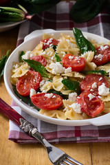 Farfalle with Tomatoes, Spinach and Cheese in a plate on a wooden table