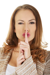 Woman placing finger on lips.