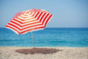 Striped beach umbrella on the beach.