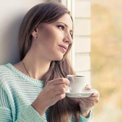 Pretty young woman drinking espresso