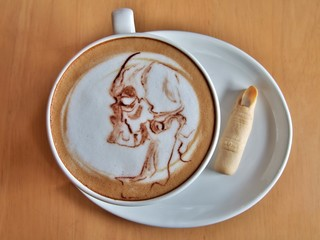 Coffee Halloween, Latte art as a skull ghost with cookie like finger.