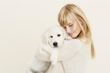 Young woman cuddling Labrador puppy