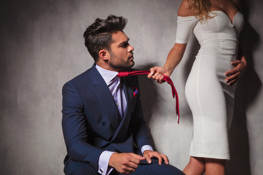 man looking at his lover while she  pulls his tie