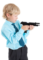 young blond boy looking into the discharged gun in hands, isolated on white background