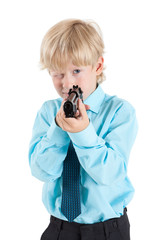 Portrait of Caucasian blond boy aiming with black gun in hands, isolated on white background