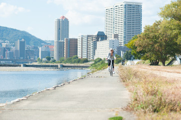 河川敷を自転車で走る日本人女性