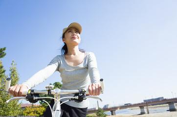 青空をバックにして自転車に乗っている日本人女性