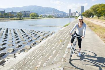 河川敷で自転車に乗っている女性