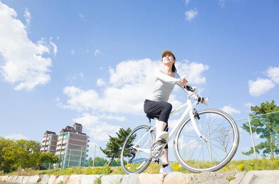 青空をバック 自転車に乗っている日本人女性