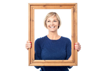 Woman looking through wooden frame