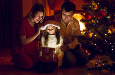 parents and cute daughter looking inside of Christmas present