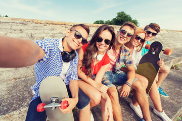 group of smiling friends with smartphone outdoors