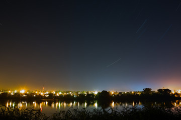 Star trail in the night sky on a background city lighting. The b