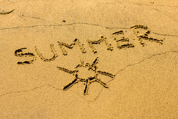 Sun and word Summer drawing on sandy beach background.