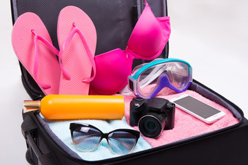 tourism concept - close up of packed suitcase full of travel ite