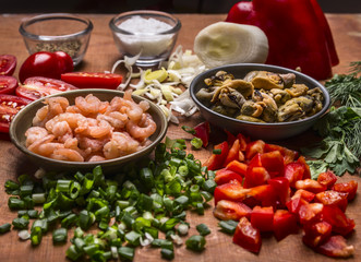 Concert cooking shrimp with mussels and vegetables seasonings pepper chopped green onions on wooden background close up