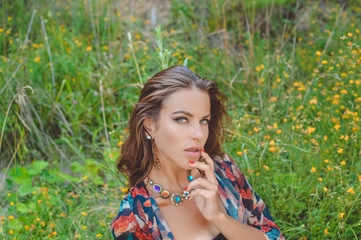 Beautiful young lady in fancy necklace sitting in countryside wildflowers