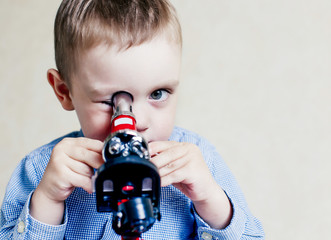 child looking in a microscope. little boy carefully studying something with microscope