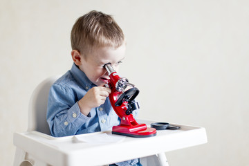 little genius. small child interested in science. boy sitting in a high chair and looks through a microscope