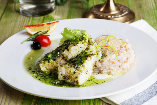 white fish with pesto sauce and meat plate in a still life