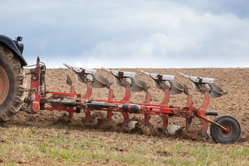 Detail of an agricultural  plough in action ploughing an overwintered fallow field ready for the planting of the spring crops