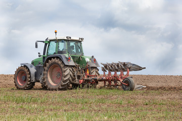 Farmer preparing a field for planting - ploughing it with an agricultural plough, close up of the tractor and implement on the skyline