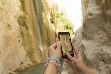 Female hands taking a photo of waterfall with a smartphone