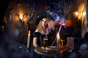 The witch is conjuring  by the candlelight.