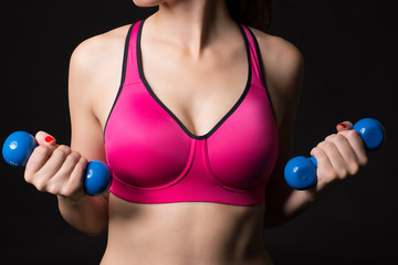 Close up view of sporty young woman wearing sports pink bra with