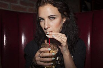 Portrait of young woman enjoying drink at nightclub