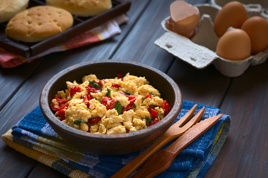 Scrambled eggs made with red bell pepper and green onion in rustic bowl, photographed with natural light (Selective Focus, Focus one third into the scrambled eggs)