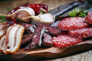 Meat appetizer platter with bacon, smoked sausage and salami on