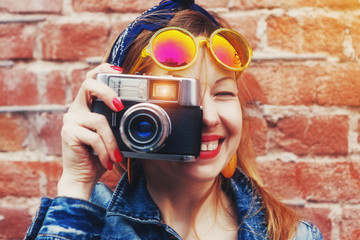 smiling girl with vintage camera taking photo with flash on bric