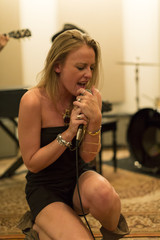 Young female singer rehearsing with her band