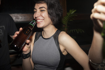 Young woman enjoying a beer at a party