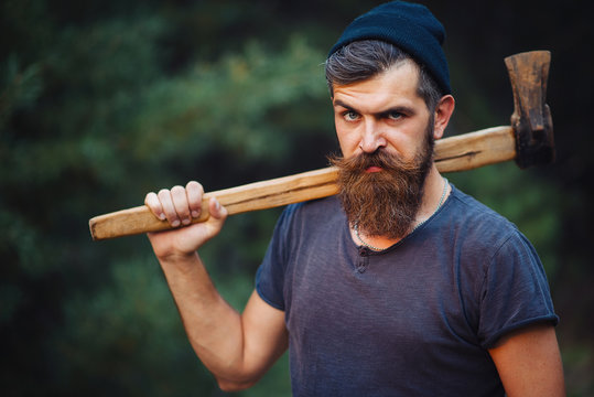 Brutal brunette bearded man in warm hat with a hatchet in the woods on a background of trees