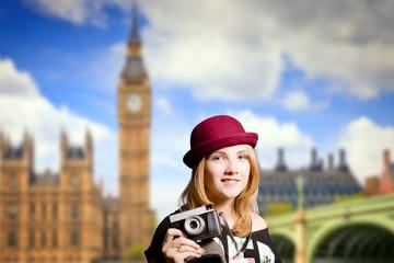 Girl in glasses making photo on London street