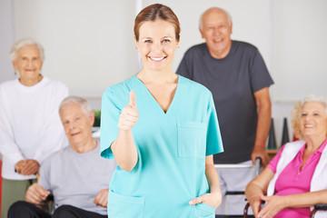 Krankenpfleger hält Daumen hoch vor Gruppe Senioren