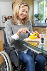 Disabled Woman In Wheelchair Prepapring Meal In Kitchen