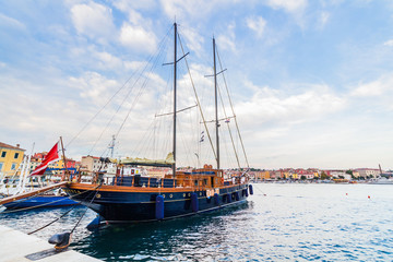 A galleass anchored among ships in the Adriatic sea with a view of the old city core buildings on the coast