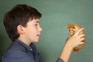 preteen handsome boy hold little red kitten