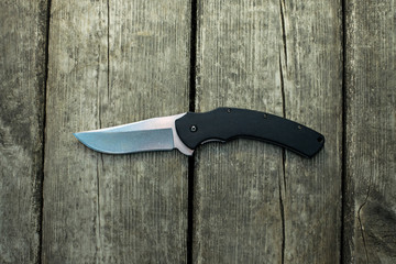 Black folding knife lying on old wooden plates