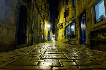 Narrow street in night of old town of Rovinj, Croatia