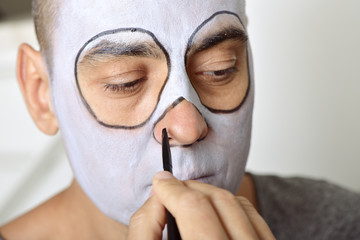 man making up himself to perform a character
