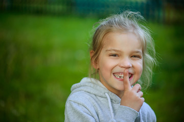 Little smiling girl in puts forefinger to lips